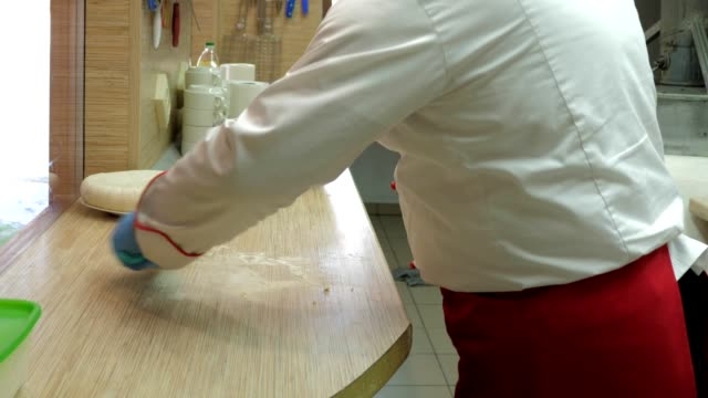 closeup cook in white uniform cleans flour from table