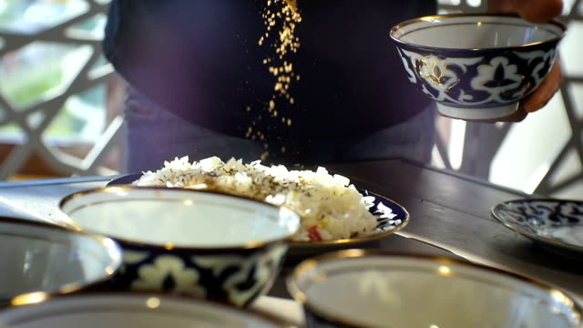 Closeup Cook Pours Spice Herbs Over Rice on Plate