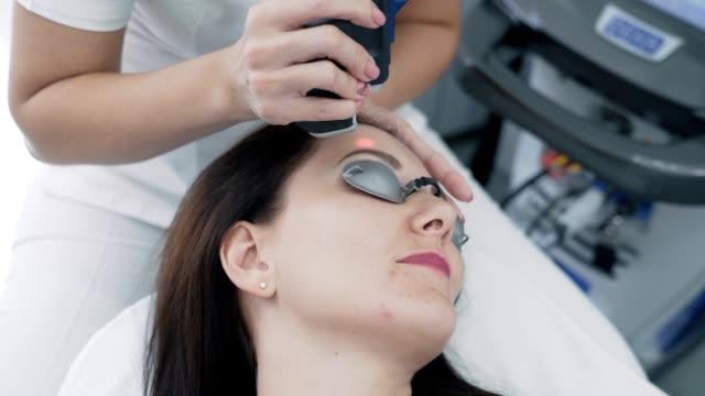 close-up cosmetologist makes hair laser removal procedure to young woman face at clinic, slow motion - kosmetyczka praca w salonie piękności filmów i materiałów b-roll