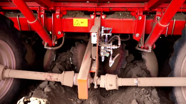 close-up, cultivator automatically plants potatoes in straight soil rows in farm field, adds mineral fertilizers to soil, for better potato growth. modern agriculture. spring sunny day - vídeo