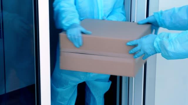 närbild, leverans av paket med medicinsk utrustning eller läkemedel till sjukhus under coronavirusutbrott. courier, i skyddsdräkt, lämnar kartonger till sjuksköterska. lastleverans under karantän - skicka datormeddelande bildbanksvideor och videomaterial från bakom kulisserna