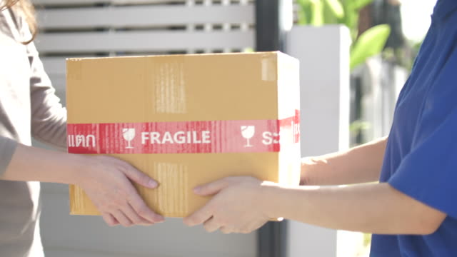 Close-up Delivery Person carrying Box for Delivery to Customer at home, Slow motion