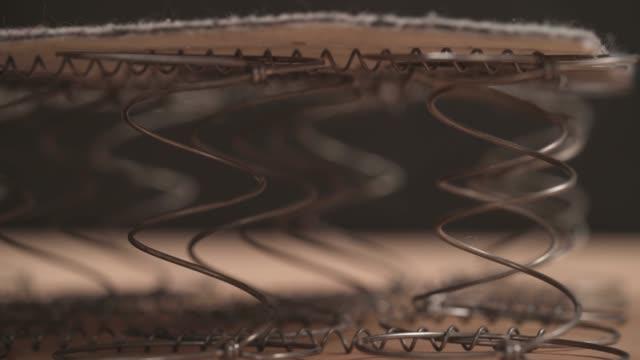 vídeos y material grabado en eventos de stock de una demostración de cerca de un carpintero profesional comprobando la flexibilidad de las bobinas offset. concepto de fabricación de muebles - colchón
