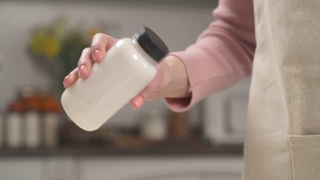 eine nahaufnahme-demonstration einer frau, die eine flasche mit kokosmilch hält und sie schüttelt. hausgemachte gesunde zubereitung - milchkrug stock-videos und b-roll-filmmaterial