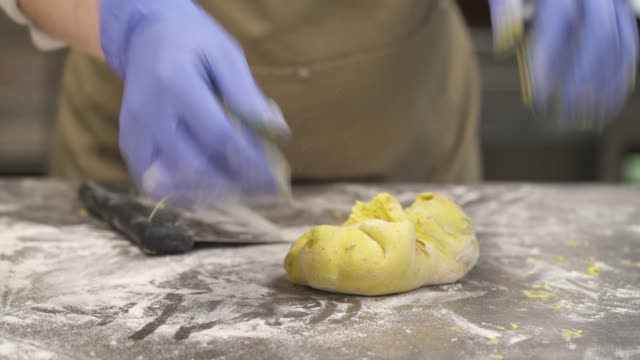 a close-up demonstration video of a bakers hands in purple culinary gloves kneading a portion of bread dough. cooking food concept - formare pane video stock e b–roll