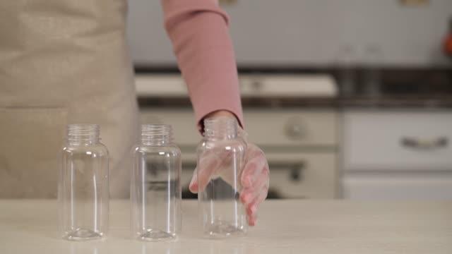 nahaufnahme-demonstrationsvideo einer frau, die saubere glasflaschen zubereist, um es zu füllen. hausgemachte zubereitung von lebensmitteln - milchkrug stock-videos und b-roll-filmmaterial