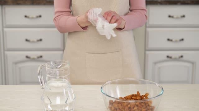 nahaufnahme-demonstrationsvideo einer frau, die handschuhe trägt und sich auf die herstellung einer mandelmilch vorbereitet. zutaten zubereiten. gesundes lifestyle-konzept - milchkrug stock-videos und b-roll-filmmaterial