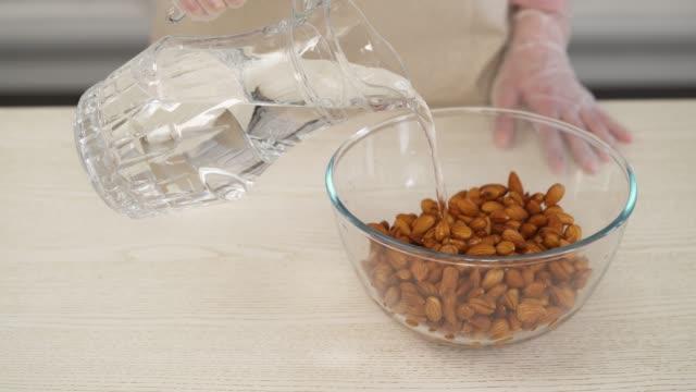 nahaufnahme-demonstrationsvideo der hand der frau hält ein glas mit wasser und gießt es in einer schüssel auf mandeln. zutaten für mandelmilch zubereiten. hausgemachte gesunde küche - milchkrug stock-videos und b-roll-filmmaterial