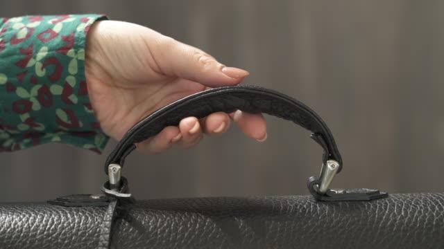 vídeos y material grabado en eventos de stock de un video de demostración de cerca de la mano de una mujer con manicura desnuda sosteniendo el mango de la bolsa y sacando la bolsa de cuero negro. elegante bolso masculino - manija