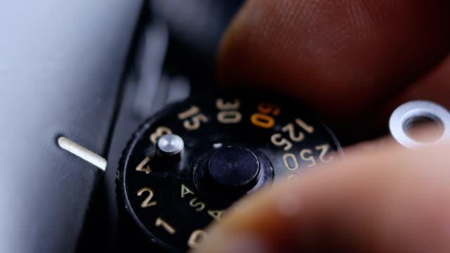 vidéos et rushes de gros détails d'une vieille caméra de film slr vintage et doigts réglant le cadran de vitesse d'exposition - cadran