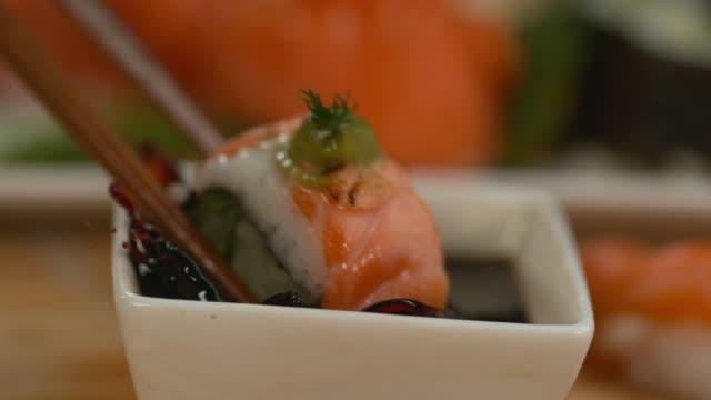 vídeos y material grabado en eventos de stock de closeup mojar el sushi en salsa de soja en camara super lenta - sushi