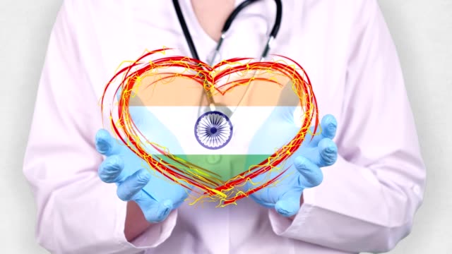 close-up. Doctor in medical white coat, blue gloves holds in hands drawn pulsating heart with India flag. Concept of doctors struggling against global epidemic, coronavirus video