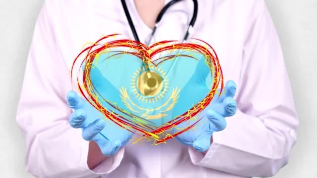 close-up. Doctor in medical white coat, blue gloves holds in hands drawn pulsating heart with Kazakhstan flag. Concept of doctors struggling against global epidemic, coronavirus - vídeo