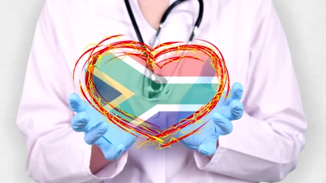 close-up. Doctor in medical white coat, blue gloves holds in hands drawn pulsating heart with South Africa flag. Concept of doctors struggling against global epidemic, coronavirus - vídeo
