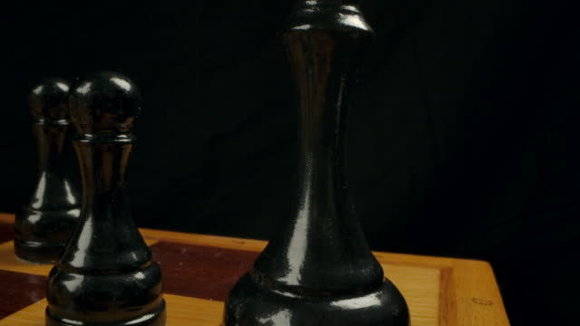 Close-up dolly macro shot of a black wooden chess King on a chessboard