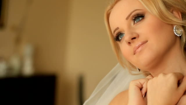 Close-up dreamy face of charming bride with elegant make-up wearing shiny diamond earrings video