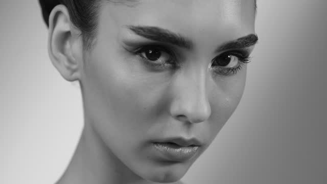 Close-up face of a beautiful young girl, eyes closed and then looking into the camera. Black and white video. video