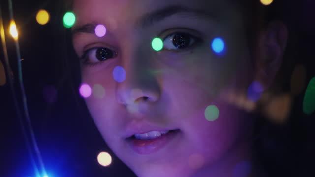 faccia ravvicinata di una ragazza attraverso luci luminose - curiosità video stock e b–roll