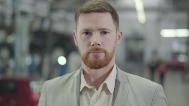 Close-up face of adult Caucasian man with brown eyes and red beard gesturing yes by shaking head, and smiling. Male car dealer posing at the background of showroom. Car dealership, car business. Close-up face of adult Caucasian man with brown eyes and red beard gesturing yes by shaking head, and smiling. Male car dealer posing at the background of showroom. Car dealership, car business. salesman stock videos & royalty-free footage