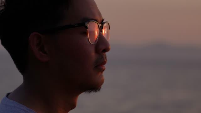 zbliżenie twarzy azjatyckiego mężczyzny w okularach patrzących na zachód słońca z odbiciem światła słonecznego - nadzieja filmów i materiałów b-roll