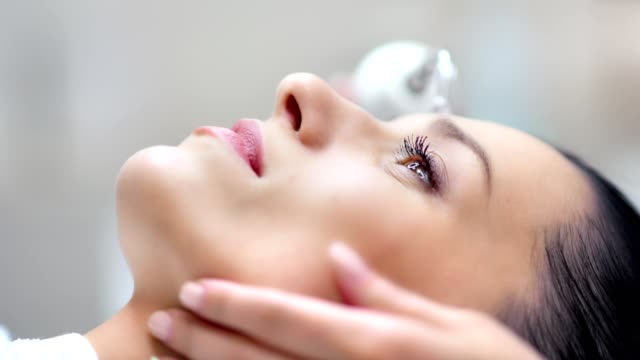 Close-up face of confident pretty woman during microdermabrasion beauty procedure using equipment Close-up face of confident pretty woman during microdermabrasion beauty procedure using hi-tech equipment. Side view female lying at cosmetology clinic ultrasonic magnetic facial cleansing beautician stock videos & royalty-free footage