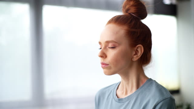 vídeos de stock e filmes b-roll de close-up face of focused redhead young woman doing breathing yogic practices at home office. - budismo