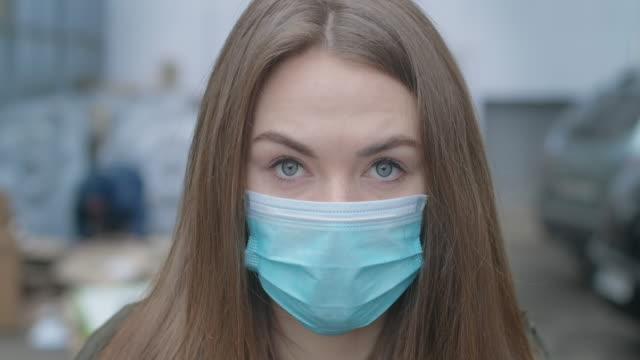 close-up face of girl in protective mask looking at camera. young beautiful brunette woman with grey eyes outdoors in city. pandemic, medicine, covid-19. cinema 4k prores hq. - covid 19 stock videos & royalty-free footage