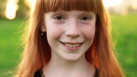 vidéos et rushes de visage de gros plan de fille heureuse de gingembre avec taches de rousseur sur fond flou - petites filles