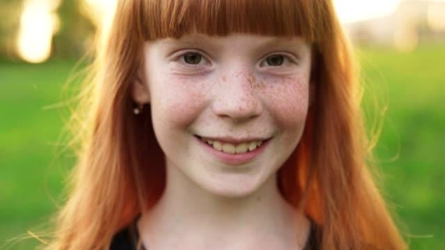 close-up face of happy ginger girl with freckles on blurred background - uśmiechać się filmów i materiałów b-roll