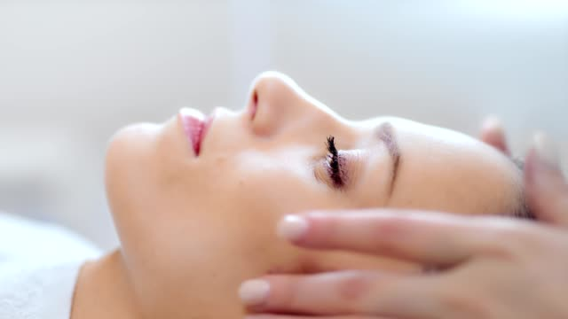 close-up face of pretty relaxing woman having good time at beauty massage salon side view - spa facial stock videos & royalty-free footage