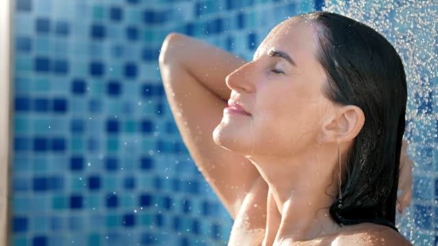 Close-up face of smiling wet woman taking outdoor shower having positive emotion slow motion