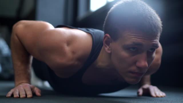 vidéos et rushes de visage rapproché du jeune homme avec le corps musculaire faisant l'exercice de push-ups. - body building