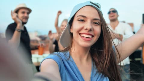 vídeos de stock e filmes b-roll de close-up face of young woman in cap taking selfie surrounded by friends at rooftop party - adolescente