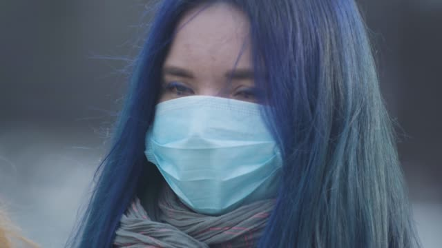 Close-up face of young woman with blue hair and blue eyes wearing protective mask. Portrait of woman standing on city street during epidemic outbreak. Hazard, danger, pandemic, coronavirus. Close-up face of young woman with blue hair and blue eyes wearing protective mask. Portrait of woman standing on city street during epidemic outbreak. Hazard, danger, pandemic, coronavirus. blue hair stock videos & royalty-free footage