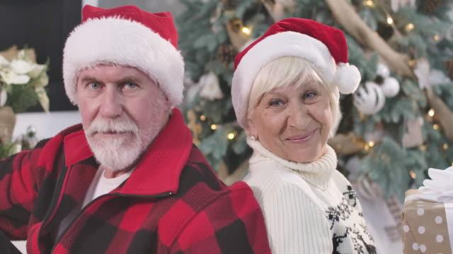 nahaufnahme gesichter des glücklichen reifen kaukasischen paar sitzen zurück zu rücken, blicke in die kamera und lächelnd. weihnachten, silvester, ewige liebe, feiertage. kino 4k prores hq. - rücken an rücken stock-videos und b-roll-filmmaterial