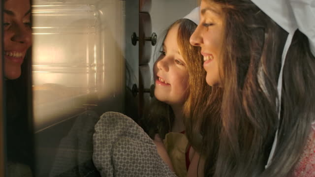 close-up faces of little caucasian brunette girl and her mother looking into oven. happy smiling family baking at the kitchen at home. cinema 4k footage prores hq. - piec przygotowywać jedzenie filmów i materiałów b-roll