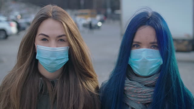 Close-up faces of two young women in protective masks looking at camera at the background of busy city street. Portrait of worried girls outdoors. Epidemic, Covid-19, illness. Cinema 4k ProRes HQ.