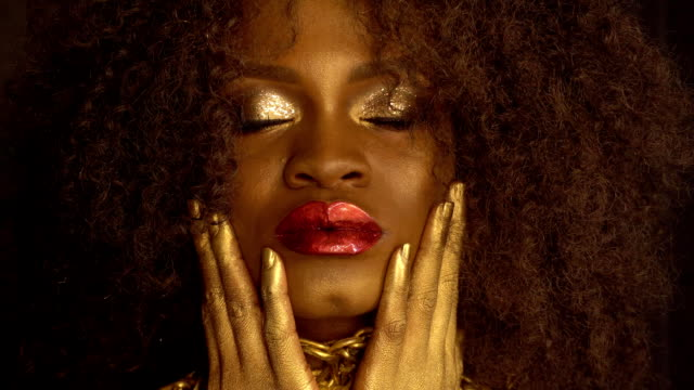 Close-up fashion portrait of young african american female model with gold glossy makeup. Face art. Black studio background video