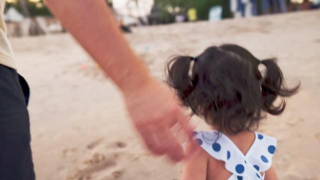 närgången far leker och går med söt dotter på semester på stranden - enbarnsfamilj bildbanksvideor och videomaterial från bakom kulisserna