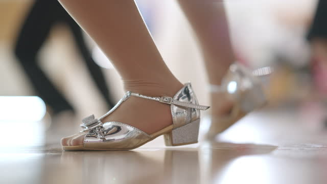 Close-up feet of Caucasian girl in silver high-heels making ballet step in slow motion. Unrecognizable children rehearsing learning dancing in dance studio indoors. Skill and art concept. Close-up feet of Caucasian girl in silver high-heels making ballet step in slow motion. Unrecognizable children rehearsing learning dancing in dance studio indoors. Skill and art concept. dance studio stock videos & royalty-free footage