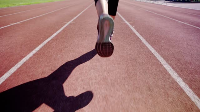 Close-up feet of unrecognizable female athlete running on track in slow motion