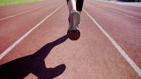 Close-up feet of unrecognizable female athlete running on track in slow motion Close-up feet of unrecognizable female athlete running on track in slow motion competition stock videos & royalty-free footage