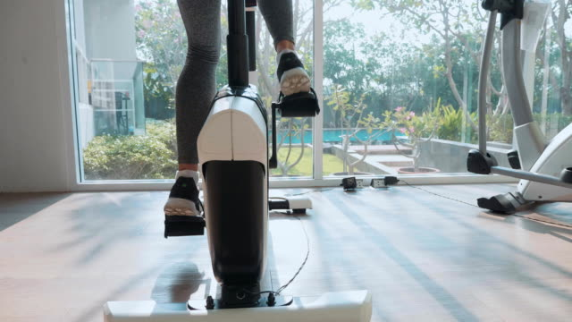 Close-up female feet riding at stationary bike at the gym in slow motion Close-up female feet riding at stationary bike at the gym in slow motion, rear view exercise bike stock videos & royalty-free footage