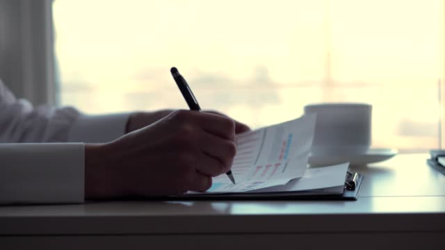 close-up, female hand, holding a black pen and writing something in documents, business woman working with graphs and diagrams, on a white desktop in the office. - бухгалтерия стоковые видео и кадры b-roll