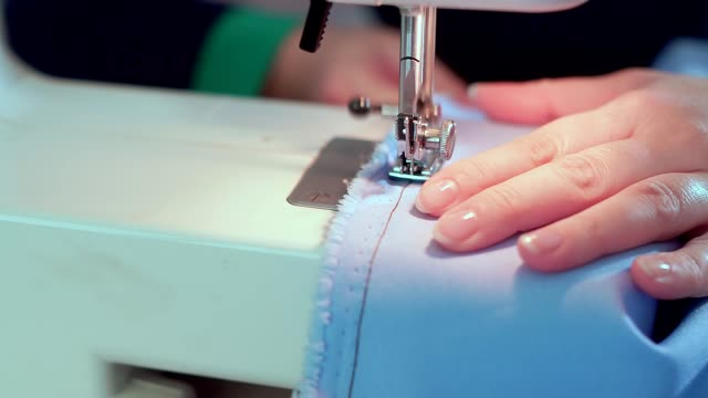 close-up, female hand on a sewing machine. she sews clothes, a needle makes a seam. slowmo - sarta video stock e b–roll