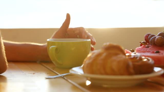 クローズ アップ女性の手はオープンエアのカフェで紅茶のカップをなでます。 ビデオ