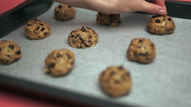 Close-up Female hands adding Chocolate Chips on top of Chocolate Chip Cookies raw dough bowls in 4K.