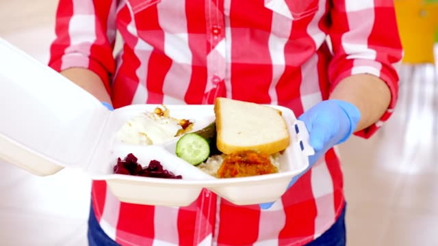 close-up, female hands in gloves hold foam lunchbox with Charity hot meal for poor, homeless people during lock down of covid19. Free food delivery. donating aid - vídeo