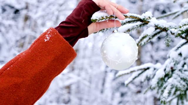 närbild kvinnliga händer i vantar händer hänga jul leksaker dekoration träd i en riktig vinter från en snötäckt gren - hänga bildbanksvideor och videomaterial från bakom kulisserna