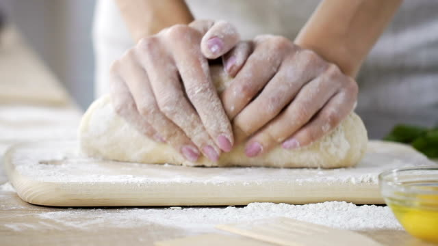 Close-up female hands kneading fresh dough at home kitchen, baking process